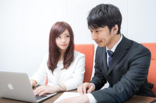 研修中パソコンの画面ではなく先輩の顔を見つめる新入社員